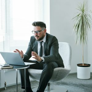 Confident businessman communicating with business partners through video chat